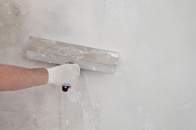 La main de l'artisan masculin dans le gant tient la truelle de construction