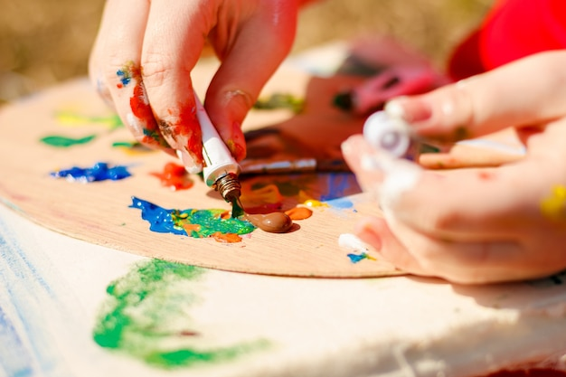 Main de l'artiste dessinant l'image et la palette avec des peintures et des pinceaux sur fond d'herbe.