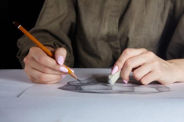 La main de l'artiste tient un gros plan au crayon et à la gomme.