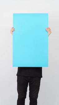 La main asiatique masculine tient le papier de couleur bleu vierge sur fond blanc.