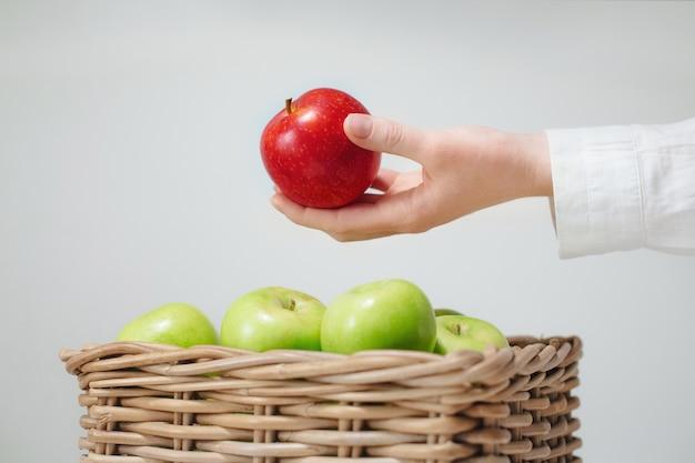 La main au-dessus du panier avec des pommes vertes et rouges
