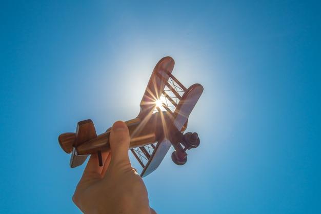 La main avec un avion en bois sur le fond du soleil éclatant
