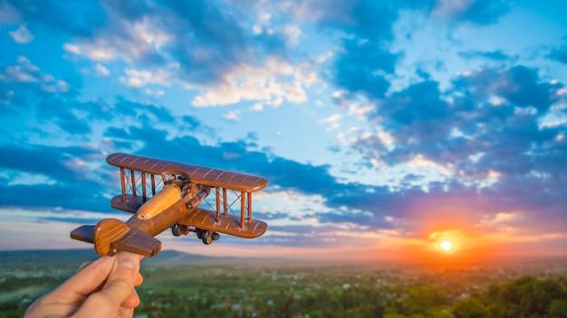 La main avec un avion jouet sur fond de coucher de soleil
