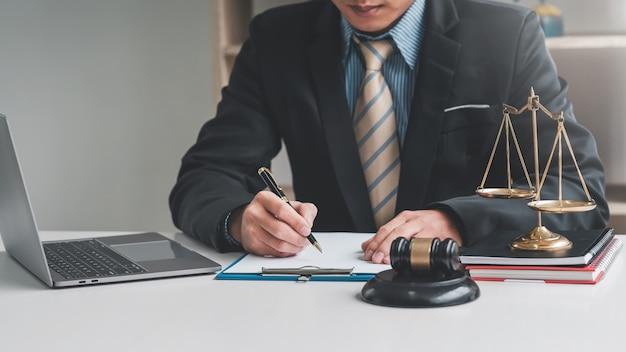 Main d'avocat tenant un stylo et des papiers à écrire, un marteau pour ordinateur portable placé au bureau.