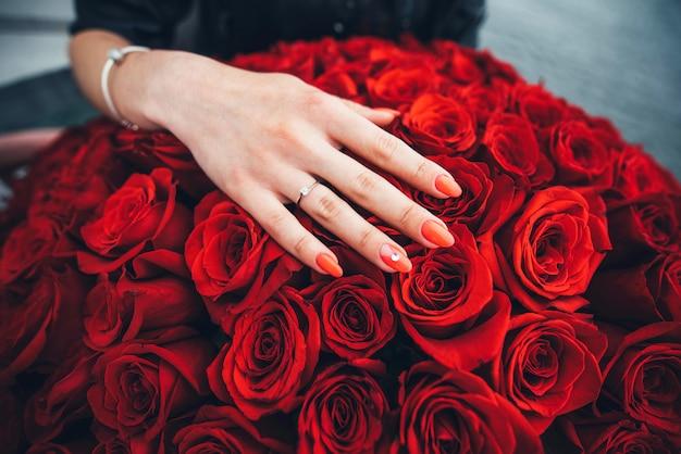 Main avec bague en diamant sur les roses rouges