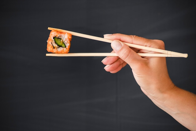Main avec baguettes et rouleau de sushi