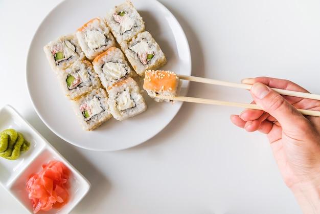 Main avec des baguettes saisissant un rouleau de sushi