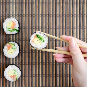 Une main avec des baguettes tient un rouleau de sushi sur un tapis de serwing en paille de bambou
