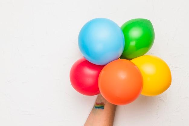 Main avec des ballons aux couleurs lgbt