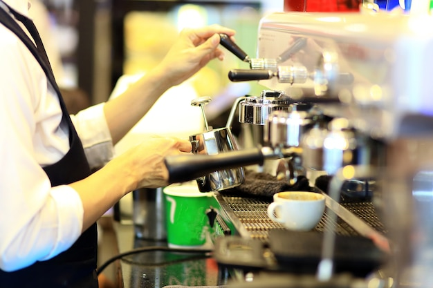 Main de barista faisant du café avec la machine à café dans le café ou le café.