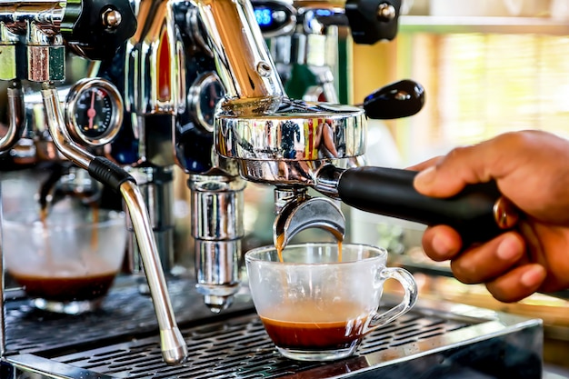 Main de barista préparant un café expresso avec la machine à café dans le café.