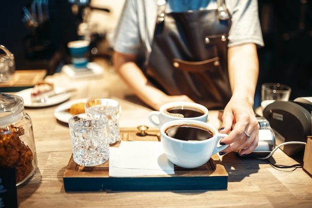 Main de barista avec tasse de café noir chaud frais