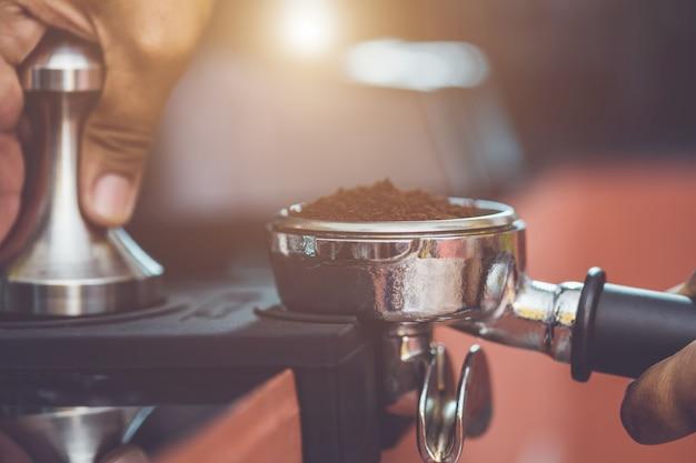Main de barista tenant un bourrage de café et préparant du café