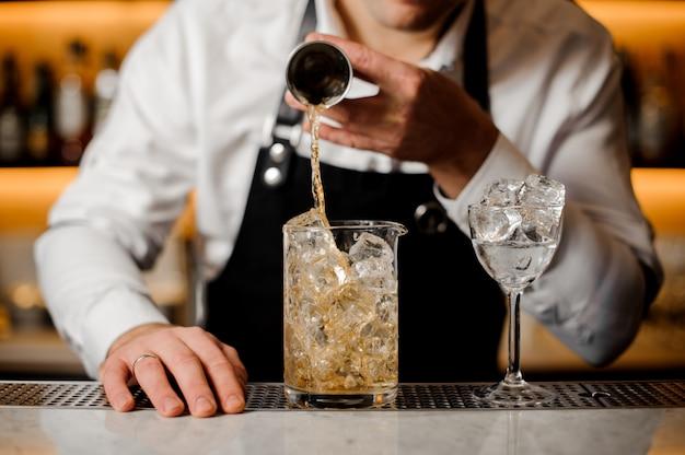 Main de barman versant une portion de boisson alcoolisée dans un verre