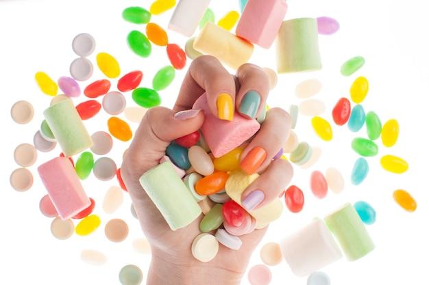 Main avec de beaux ongles tenant des bonbons assortis