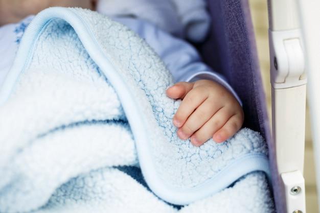 Main de bébé sur une couverture blanche