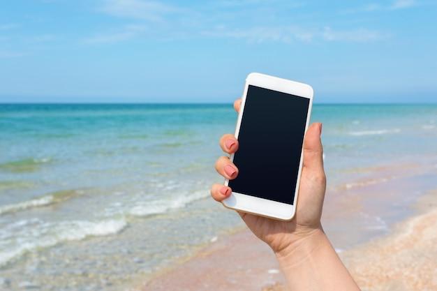 Main de belle femme à l'aide d'un téléphone intelligent sur la plage
