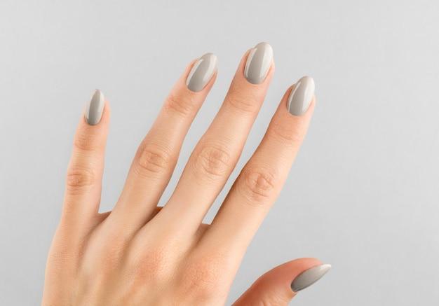 Main de belle femme avec manucure gros plan sur gris.