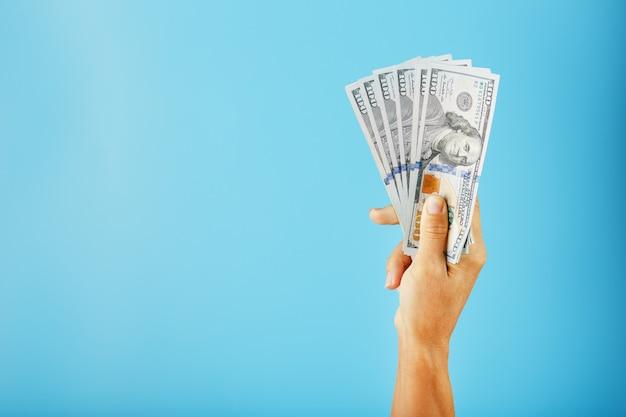 Une main avec des billets de cent dollars sur bleu.