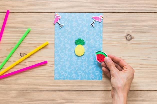 Main bleue décorer une carte bleue avec autocollant sur fond en bois
