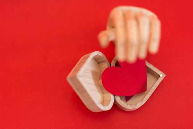 Main en bois avec coeur rouge sur une table rouge
