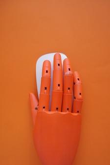 Main en bois dans un ordinateur mause avec orange