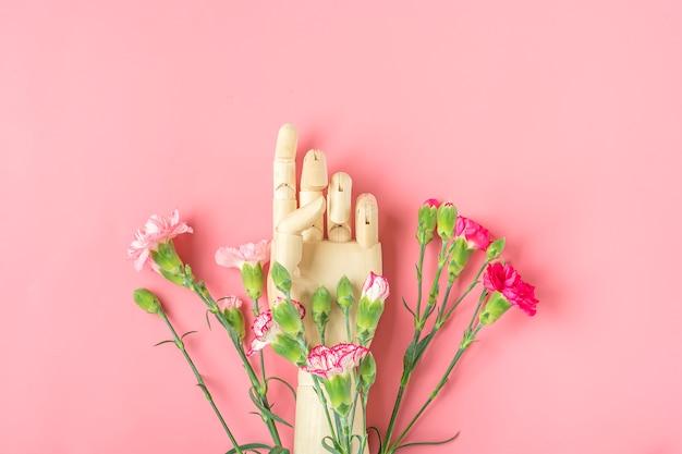 Main en bois et différents œillets sur fond rose lay plat