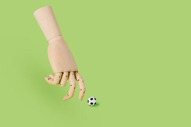 Main de bois jouant avec un ballon de football sur fond vert. concept de football et de sport.