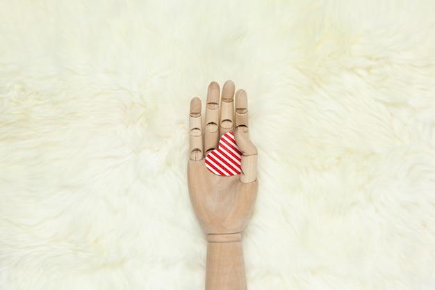 Main en bois à la mode détient coeur rayé rouge sur tapis de fourrure blanche