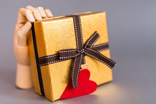 Main en bois tenant une boîte cadeau avec coeur