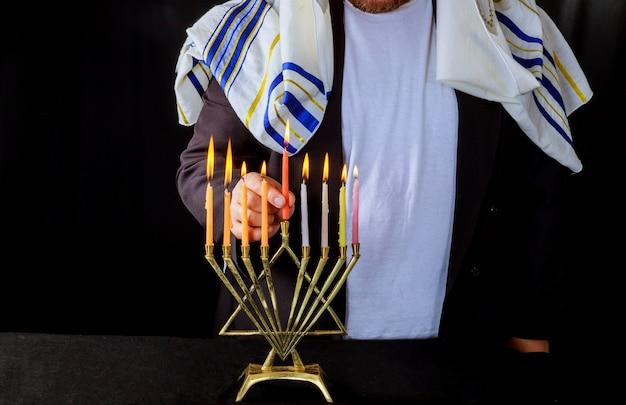 Main des bougies allumées sur les symboles hannukah de la fête juive de la ménorah