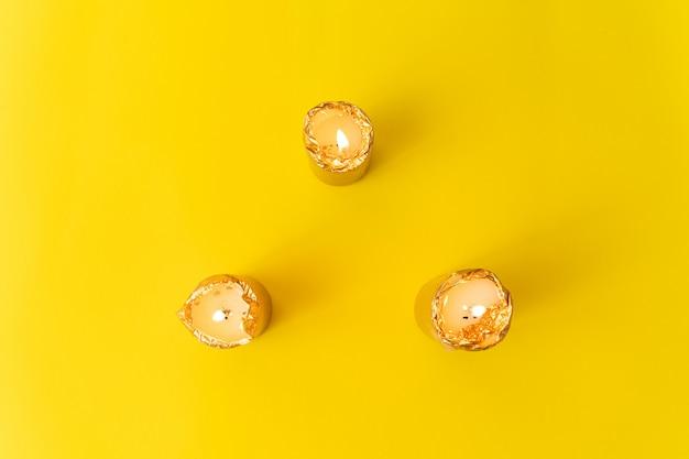 La main avec des bougies dorées sur une surface jaune. wellnes, magie, concept relax.