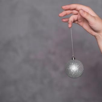 Main avec boule de noël sur fil