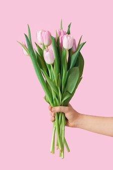 Main avec bouquet de belles tulipes sur fond de couleur
