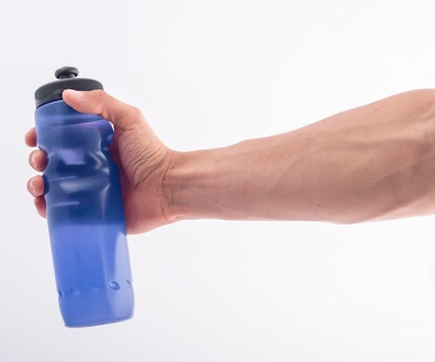 Main avec une bouteille bleue