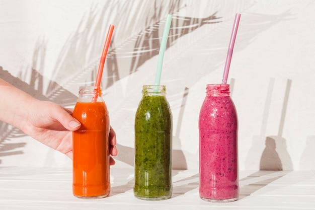 Main avec des bouteilles de boissons colorées