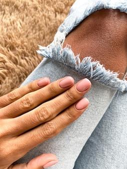 Main bronzée d'une femme avec une manucure douce beige-rose, couvrante de vernis gel