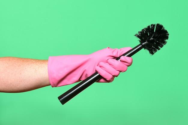 Main avec brosse à gants sur fond vert