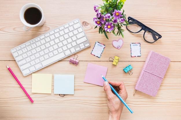 Main sur le bureau mignon avec le clavier du café et stationnaire
