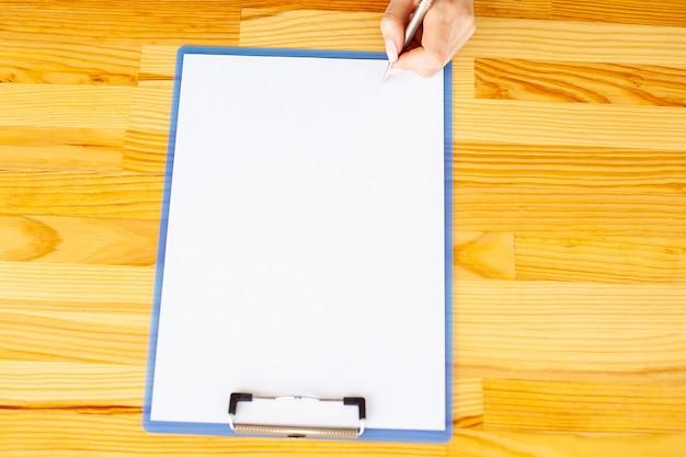 Main de bureau tenant un dossier avec un papier de couleur blanche sur le fond de la table en bois.