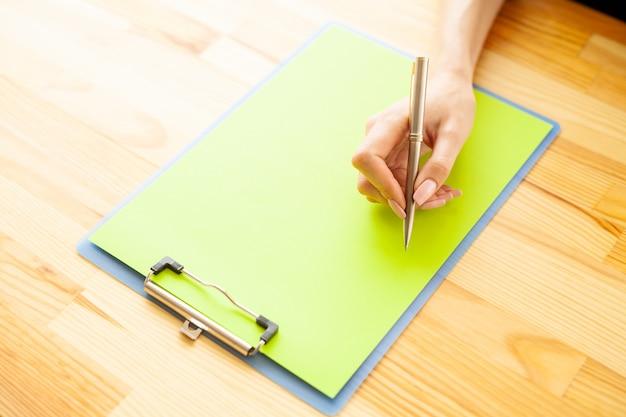 Main de bureau tenant un dossier avec un papier de couleur verte et un stylo sur le fond de la table en bois
