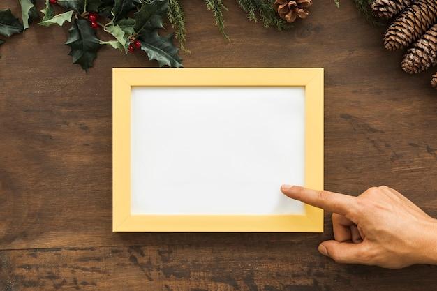 Main avec cadre photo entre chicots et brindilles