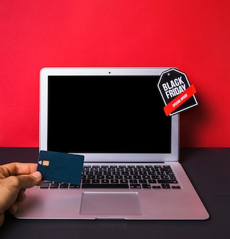 Main avec carte de crédit près d'un ordinateur portable avec signe