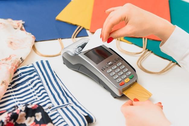 La main avec une carte de crédit à travers le terminal pour la vente au supermarché
