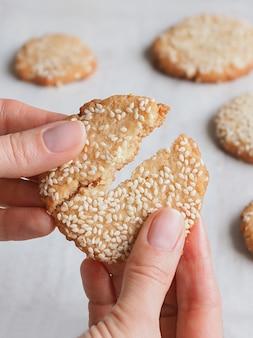 La main casse les délicieux biscuits frais au sésame.