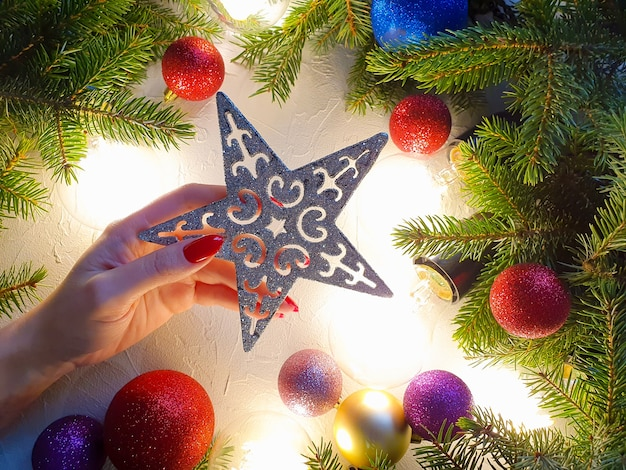 Main caucasienne féminine avec des ongles rouges tenant une étoile de noël.