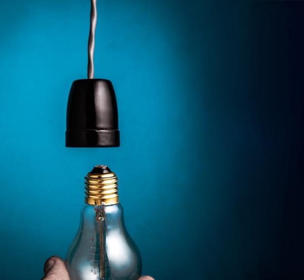 Main changeant une ampoule de filament de style edison antique sur fond bleu foncé.