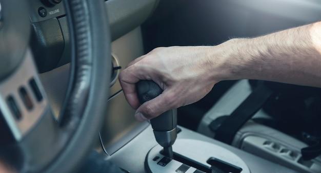 Main sur le changement de voiture manuel