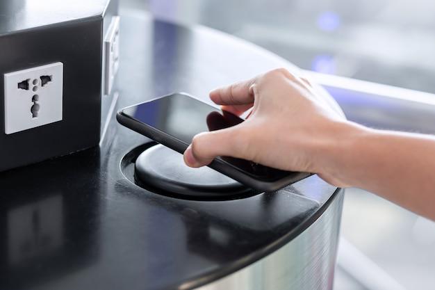 Main de charge de la batterie dans le smartphone par chargeur sans fil