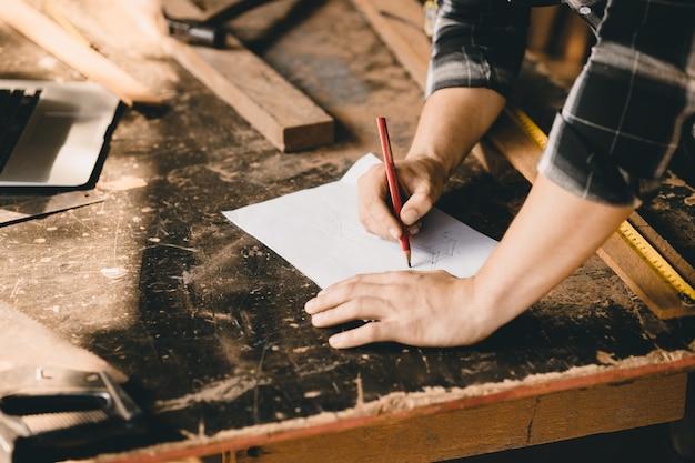 Main de charpentier dessin croquis design rêve meubles en bois en papier dans la table d'atelier en bois.
